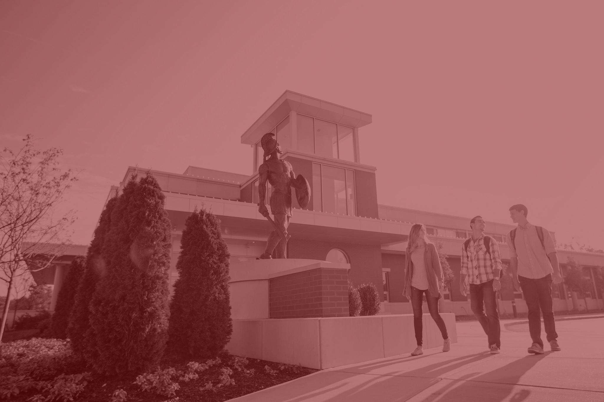Students walking past MBU's bronze Spartan statue