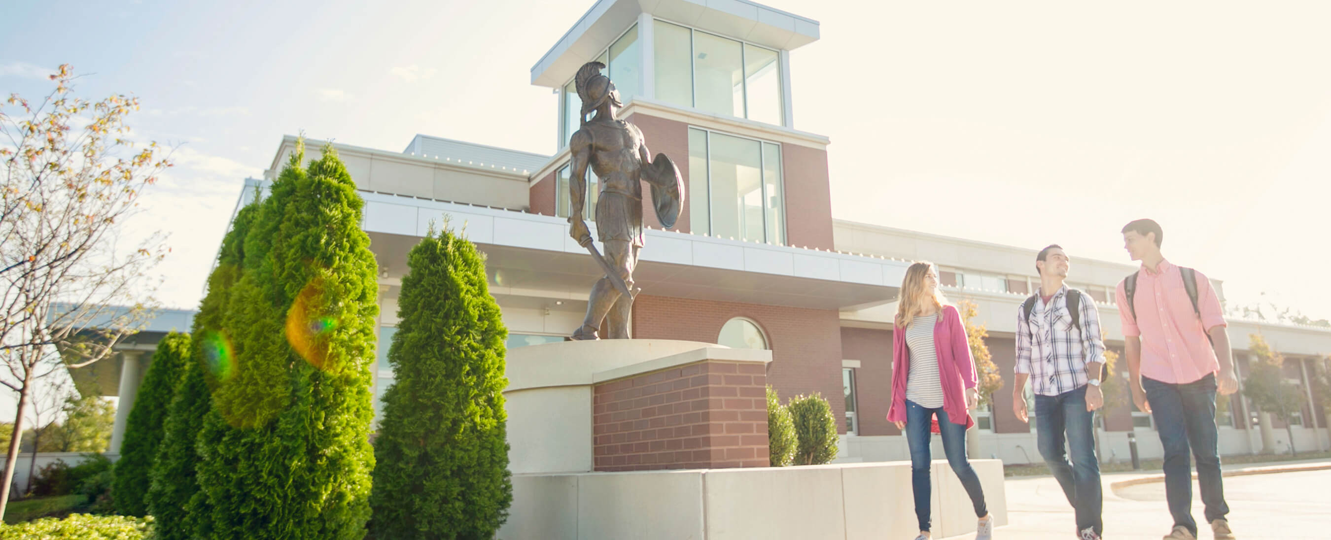 Students walking past MBU's Spartan statue on a bright day