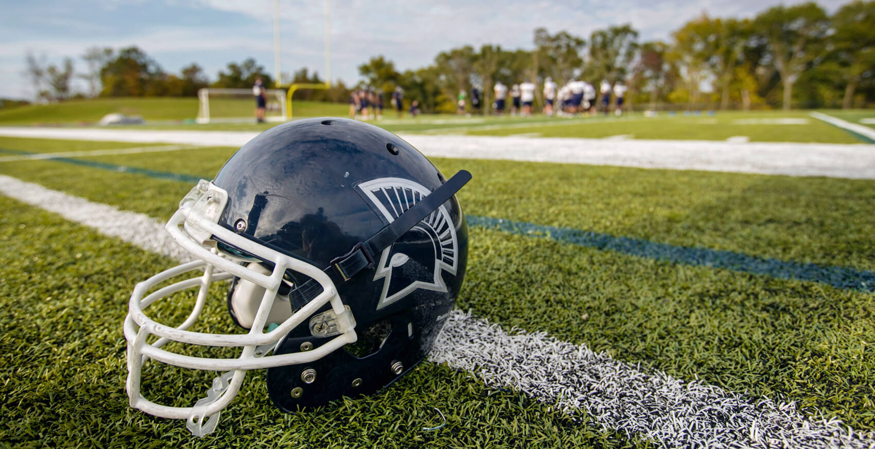 MBU Spartans helmet upright on a football field
